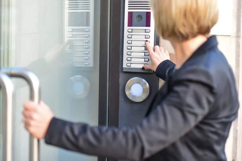 Woman pushing an intercom button