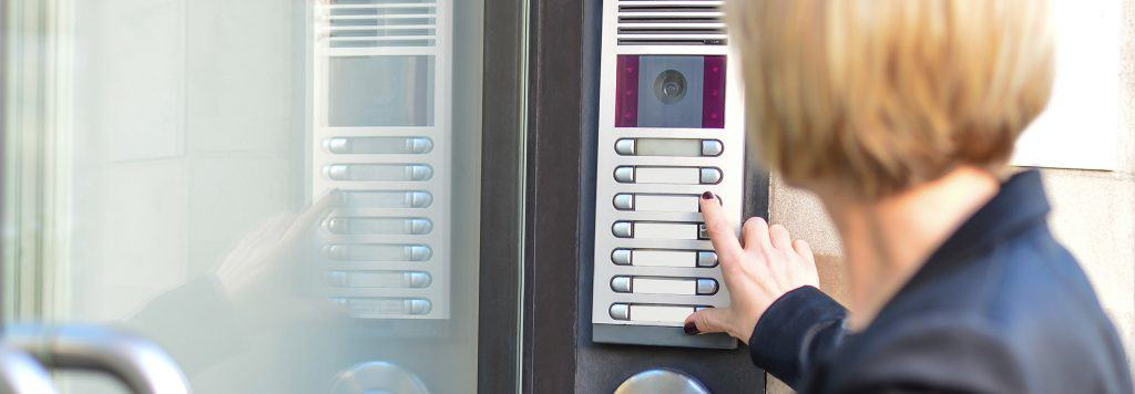 Lady using door buzzer entry system.