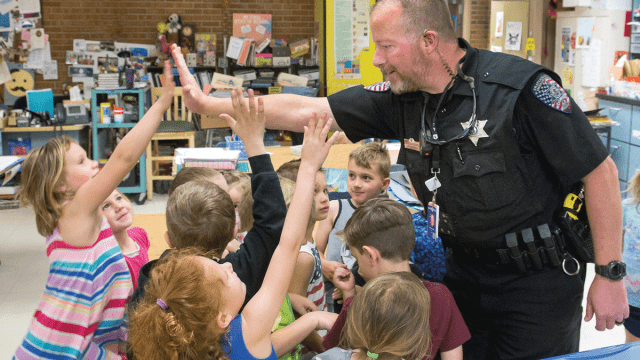 School Resource Officer giving high five to students.