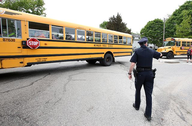 Police officer approaching school bus.